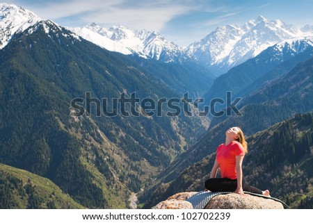 The young woman is doing a yoga asana �¢??Pose of pigeon�¢?� on the summit. On the background is a range of high tops of mountains. - stock photo