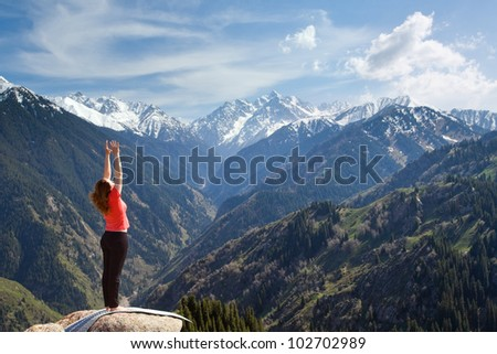 The young woman is doing a yoga asana �¢??Sun Salution�¢?� on the summit. On the background is a range of high tops of mountains. - stock photo