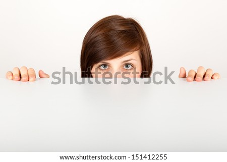 The young woman is hiding anxious behind the table