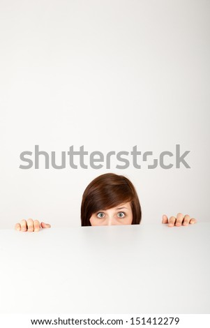 The young woman is hiding anxious behind the table - stock photo
