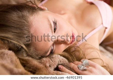 The young woman lays on fur.