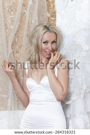 The young woman near wedding dress dreams about wedding - stock photo