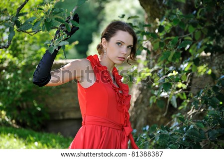 The young woman on walk in park near a tree - stock photo