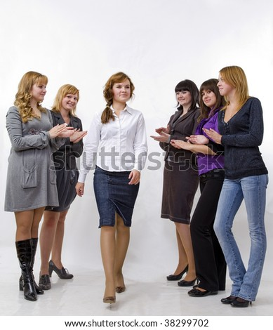 The young woman passes by group of women which clap