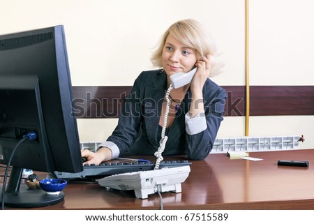 The young woman the chief works at office behind a table - stock photo