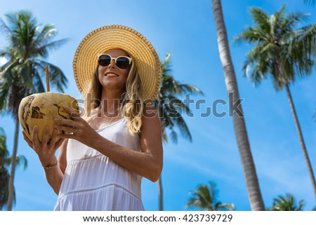 The young woman who is drinking coconut milk on under palm trees and considering copy space, being in a hat and sunglasses - stock photo