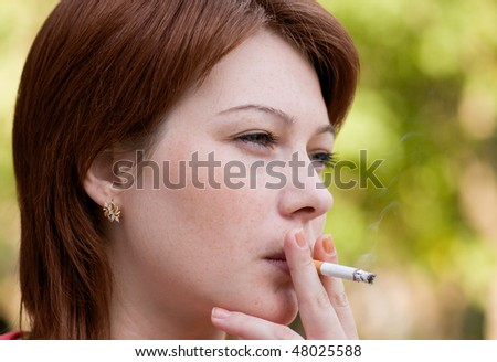 The young woman who is smoking a cigarette and carrying away a smoke in air - stock photo