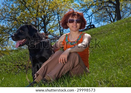 The young woman with black labrador on a green grass - stock photo