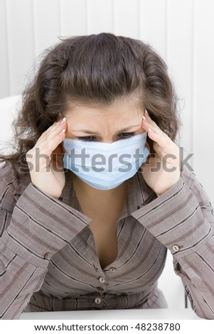 The young woman with sad eyes in medical mask keeps for sick head