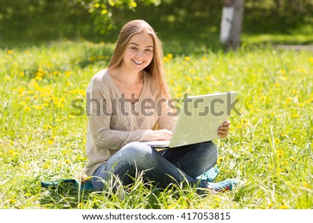the young woman with the laptop on a grass in park