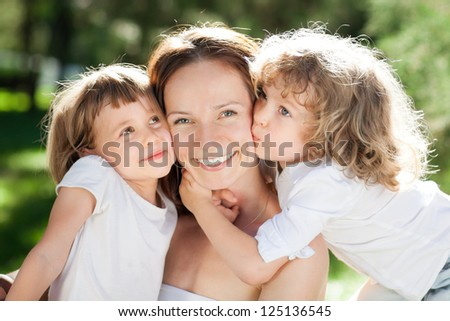 The young woman with two little girls in park - stock photo