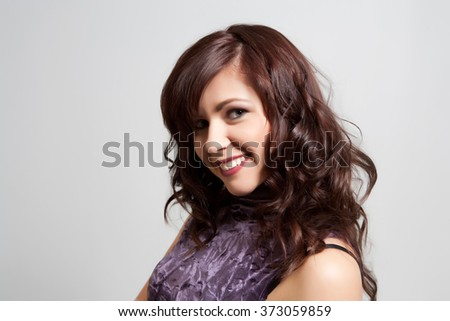 The young women. Studio shoot. Beautiful face. Brown hair. The girl with sharming look dressed in a purple dress.