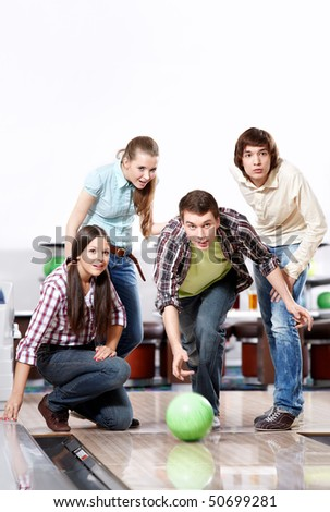 The youth observes as the young man throws a sphere for bowling - stock photo