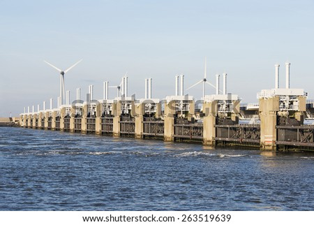 the zeelandbrug  deltaworks in holland at the Oosterschelde river to protect holland form high sea level, this is near the dutch museum neeltje jans with windmills as background - stock photo