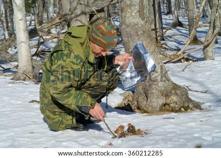 The zoologist explores an amur (Siberian) tiger in far-eastern taiga. - stock photo