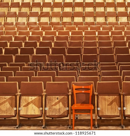 Theater seats, front side, one red seat, seventh place, first row, background - stock photo