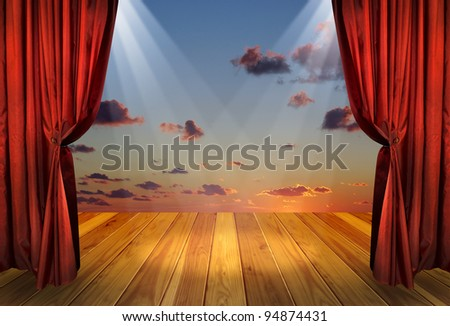 Theater stage with red curtains and spotlights on the stage wooden floor. Theatre interior with decorations of the dramatic sky wallpaper. - stock photo