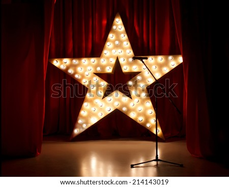 Theater stage with red curtains,microphone  and golden lightstar on background - stock photo
