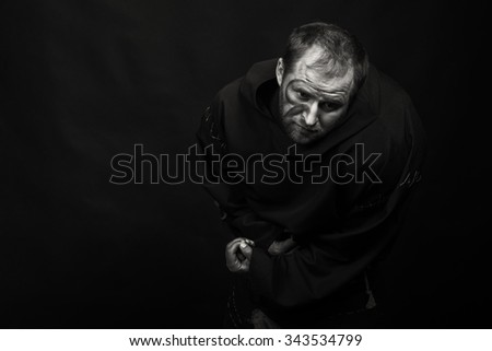 Theatrical actor Posing for the camera in the image feeble beggar. Artfully applied makeup and beautiful theatrical costume. Game actor and decorations complement the image of a beggar.  - stock photo