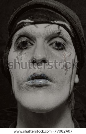 theatrical actor with dark makeup on her face