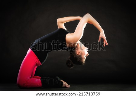 Theatrical art. Full length of brunette girl actress doing acting exercise on black. Woman performing on theater stage. - stock photo