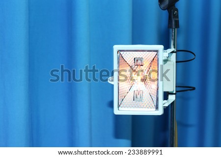 theatrical lighting appliance over the blue curtain background - stock photo