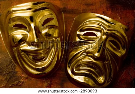 theatrical mask of tragedy and comedy over a grunge brown background - stock photo