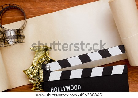 Theatrical masks and movie clapper on wooden background - stock photo