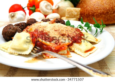 Thee cheese ravioli with Parmesan cheese sprinkled on top, small meatballs on the side. Fresh vegetables, cheese and bread in the background.