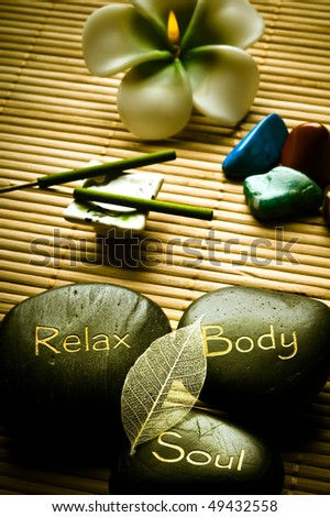 thee massage stones - relax, body, soul - and candle, aroma sticks and healing stones like a concept for wellness, body care, reiki and yoga symbols - stock photo