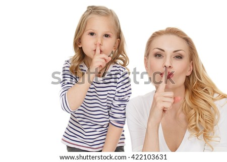 Their secret. Beautiful mother with her little daughter making shushing gesture looking to the camera at the studio on white background. - stock photo