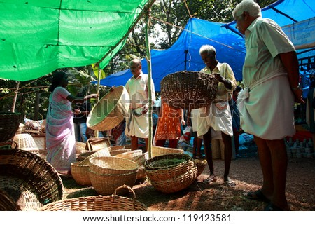 THELLIYOOR, INDIA - NOV 20 : A woman sells her products at a Rural exhibition on November 20, 2012 in Thelliyoor, India. The exhibition was held to promote Kerala's retro style house hold items