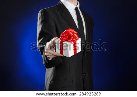 Theme holidays and gifts: a man in a black suit holds an exclusive gift in a white box wrapped with red ribbon and bow on a dark blue background in studio - stock photo