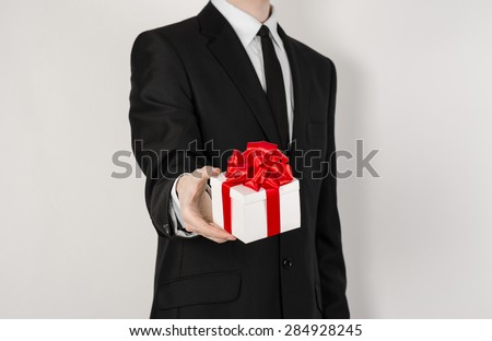 Theme holidays and gifts: a man in a black suit holds an exclusive gift in a white box wrapped with red ribbon and bow isolated on a white background in studio
