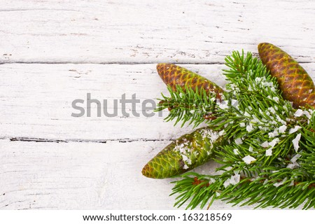 Theme New Year holidays and Christmas Green spruce branches with cones on a white background painted old wood planks as background - stock photo