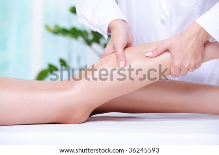 Therapeutic massage for the female beautiful leg by beautician in the spa salon - stock photo