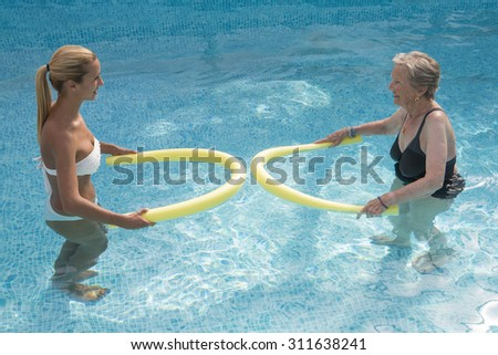 Therapist and  senior woman  doing aqua fitness  with swim noodles - stock photo