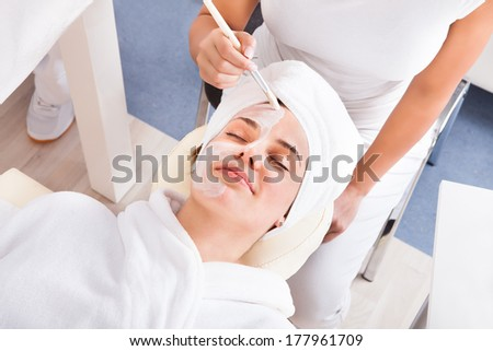 Therapist Applying A Face Mask To A Beautiful Young Woman In Spa - stock photo