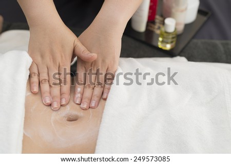 Therapist applying cream on woman's stomach - stock photo