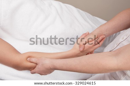 Therapist doing a  deep tissue massage on of a woman's right forearm
