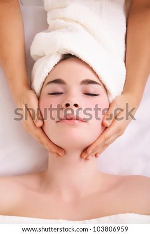 Therapist doing face massage on woman in the spa salon - stock photo