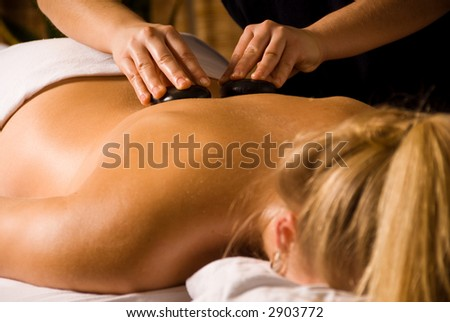 therapist giving a hot stone massage cute blond - stock photo