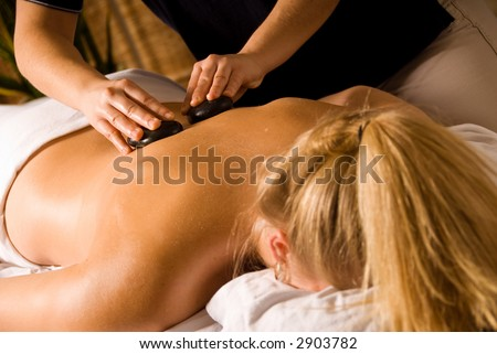 therapist giving a hot stone massage to woman - stock photo