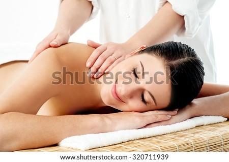 Therapist giving massage to woman - stock photo
