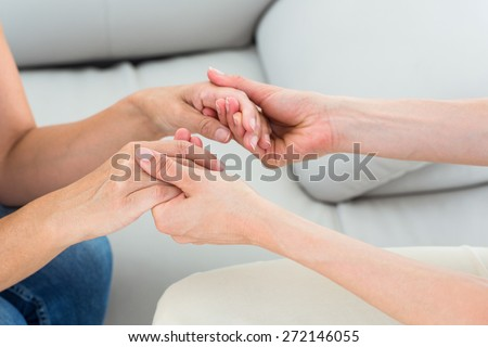 Therapist holding her patients hands on white background - stock photo
