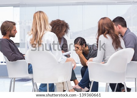 Therapist listening a woman crying during group therapy - stock photo
