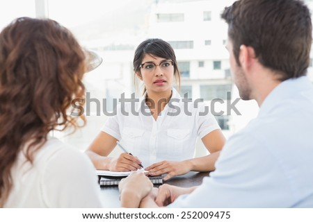 Therapist listening her patients and taking notes in the office