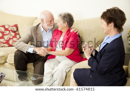 Therapist looks on as a senior couple she's been counseling works out their issues. - stock photo