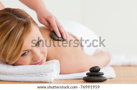 Therapist making a massage to a beautiful blond-haired woman in a spa center