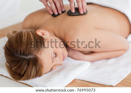 Therapist making a massage to a cute blond-haired woman in a spa center